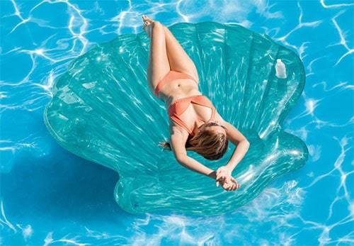 Femme sur matelas coquillage piscine